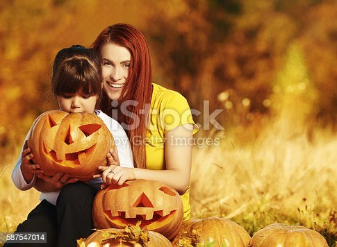 lifestyle shot of mother with her daughter holding Halloween pumpkin and smiling, enjoying great time together in autumn day.