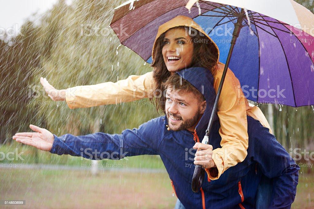 Let's hide under an umbrella in rain stock photo