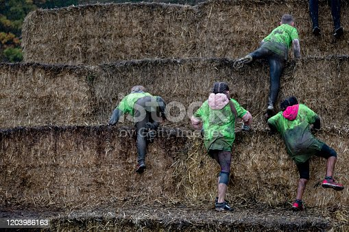 A rear view of the team of youngsters climbing up the haystacks as part of the intense tough mudder obstacle course.