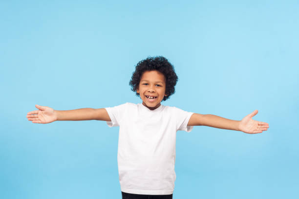 Let's hug. Portrait of friendly hospitable little boy with curls in white T-shirt smiling happily and holding hands wide open to embrace stock photo