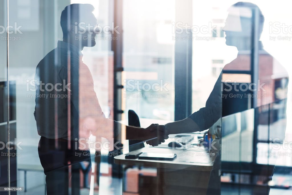 Let's join forces and claim greater successes Shot of two businessmen shaking hands in an office Adult Stock Photo