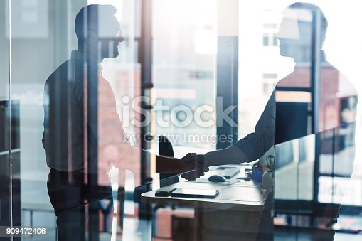 Shot of two businessmen shaking hands in an office
