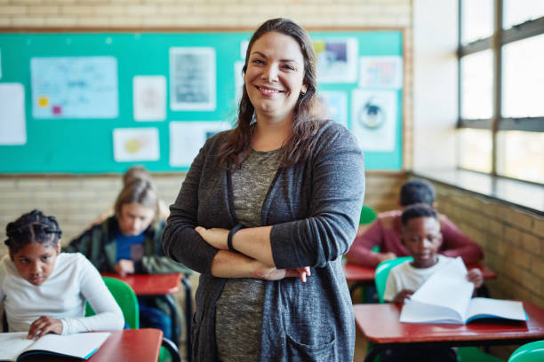 Lets learn something new today Shot of a confident young woman teaching a class of young children at school instructor stock pictures, royalty-free photos & images