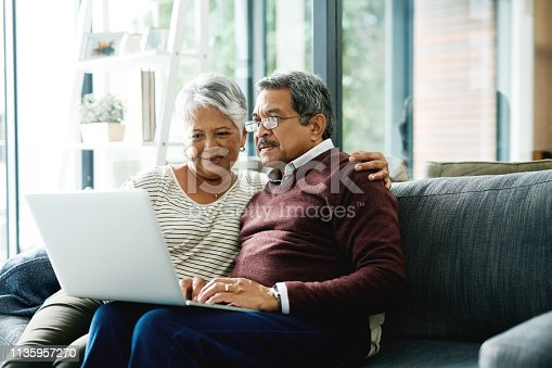 Shot of a mature couple using a laptop while relaxing at home