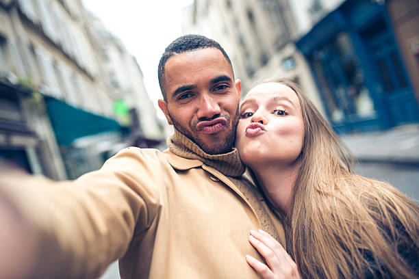 Let's make a duckface Young couple taking a selfie on city street in Paris, France. They are making faces, looking at camera, smiling. puckering stock pictures, royalty-free photos & images