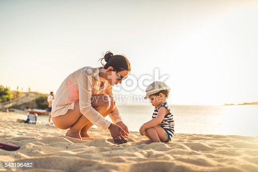 Mother and her child playing on a beach with sand