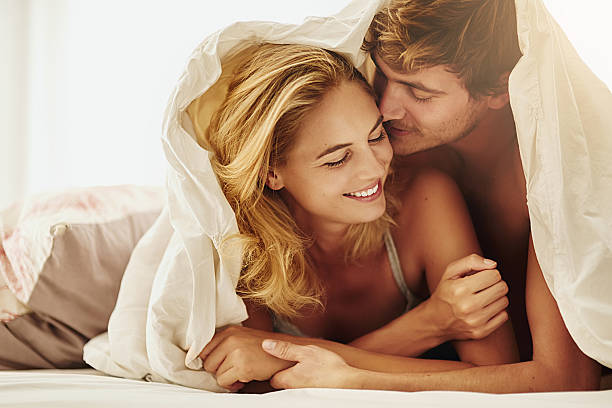 Let's make beautiful love Shot of a young couple sharing an intimate moment under the covers in bed real couples making love stock pictures, royalty-free photos & images