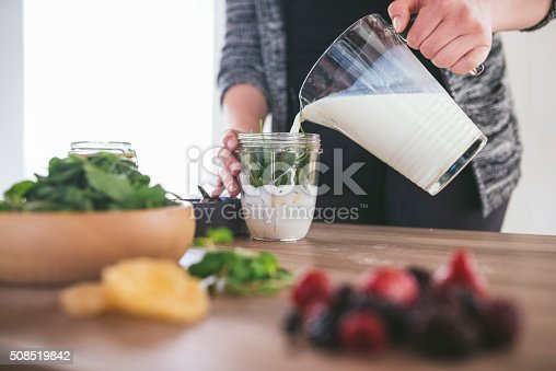 A close up of a young woman pouring milk into a cup