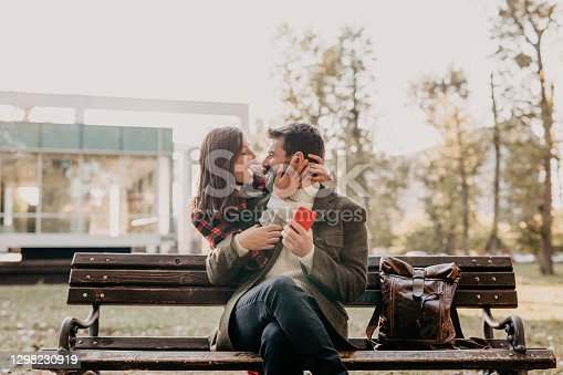 A photo of a handsome guy with a beard sitting on a bench in the park and holding a phone while looking at the beautiful woman that came from behind and hugged him with a big smile and enjoyment. They're both being stylishly dressed. Looking at each other with joy, nose to nose.