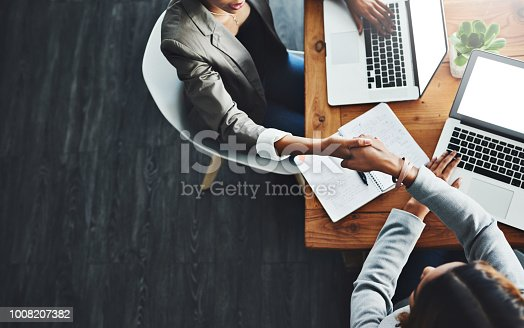 High angle shot of two businesswomen shaking hands in an office