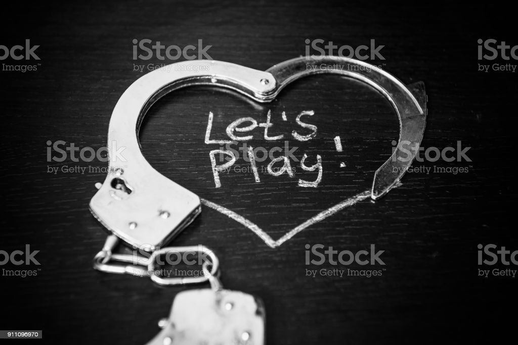 Lets play bdsm. Handcuffs for role-playing games like heart. Handcuffs with caption on black background. stock photo