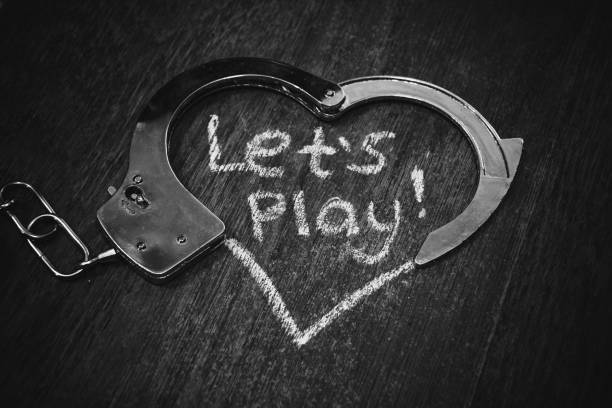 Lets play bdsm. Handcuffs for role-playing games like heart. Handcuffs with caption on black background. Metal handcuffs on dark background with caption. bdsm concept. Handcuffs for love games sex toy stock pictures, royalty-free photos & images