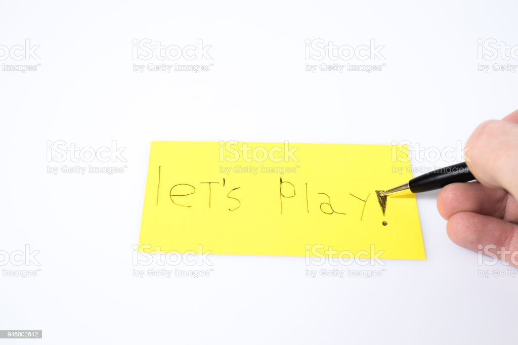 Let's play handwrite with a pen and a hand on a yellow paper composition stock photo