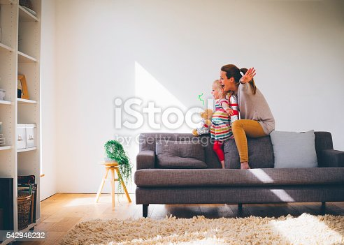 Mother and daughter are playing pretend on the sofa on the sofa in their living room. The little girl and her mum have their arms wide pretending to fly, they both look very happy.