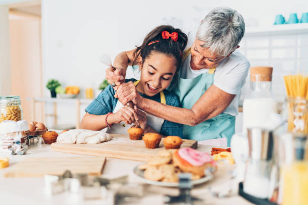Let's put the chocolate icing together! Grandmother and granddaughter preparing cupcakes together making a cake stock pictures, royalty-free photos & images