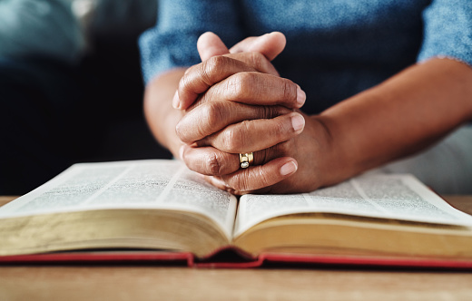 Closeup of an unrecognizable person's hands held over a bible at home during the day