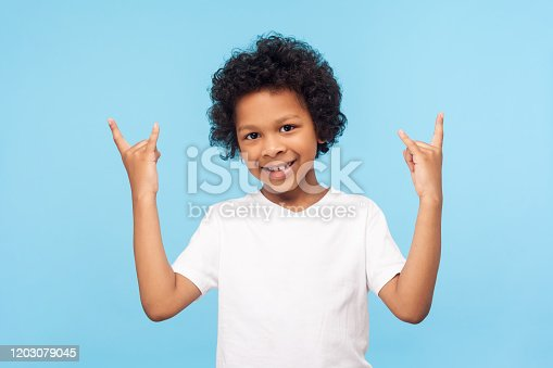 Let's rock! Portrait of joyful funky little boy with curly hair in white T-shirt showing rock and roll gesture and smiling, making crazy cool symbol with hands. studio shot isolated on blue background