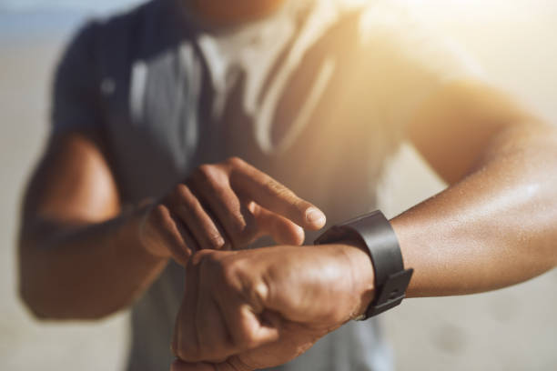 Let's see how I did today Closeup shot of an unrecognizable man checking his smartwatch while exercising outdoors diad stock pictures, royalty-free photos & images
