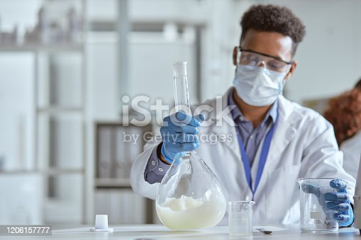 Shot of a young scientist conducting an experiment in a lab