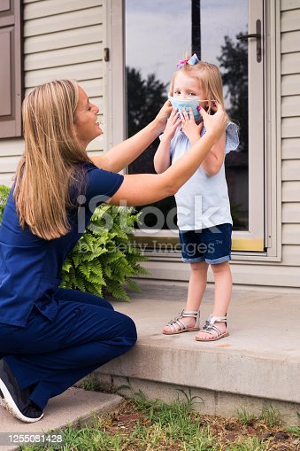 A pretty nurse in scrubs attempts to put a face mask on her 3 year-old daughter on the front step of her house before she leaves for work, Indiana, USA