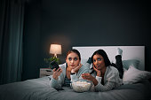 Shot of two young women eating popcorn while watching a movie at home