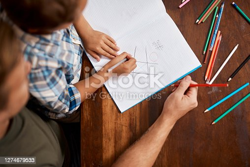 Shot of a boy playing Tic-Tac-Toe with his dad at home