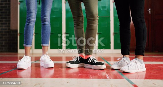 Low angle shot of a group of unrecognizable student's shoes with them standing and waiting to go to class