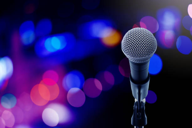 Let's sing Close up microphone  on stage in concert hall or conference ball room. Let's sing spokesperson stock pictures, royalty-free photos & images