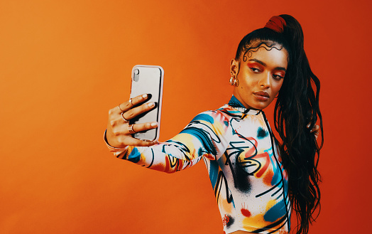 Studio shot of a fashionable woman taking a selfie against a orange background