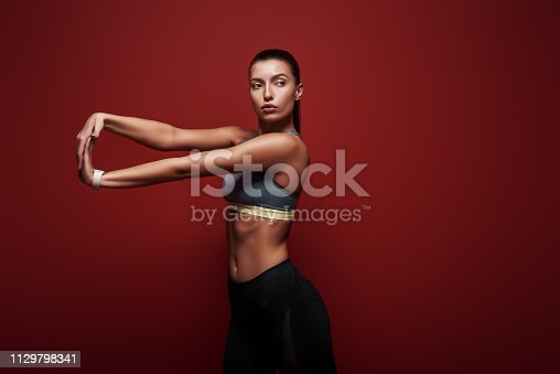 istock Let's stretch Sportswoman standing over red background, stretching her arms 1129798341