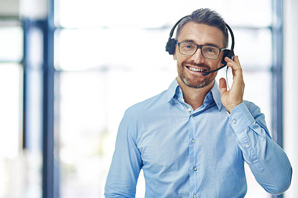 Let's talk Portrait of a friendly mature businessman wearing a headset in an office hands free device stock pictures, royalty-free photos & images