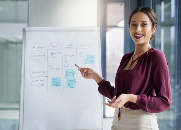 Let's talk strategy Portrait of a young businesswoman delivering a presentation in a modern office presenter stock pictures, royalty-free photos & images