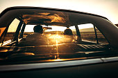 Romantic getaway of young couple, sitting in car and driving on sunset, rear view, in car from 1980 year