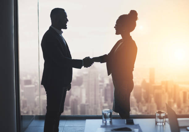 Let's work towards realizing our big ambitions together Silhouetted shot of two businesspeople shaking hands in an office business handshake stock pictures, royalty-free photos & images