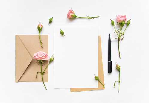 Letter and envelope decorated with pink roses. Holiday flat lay