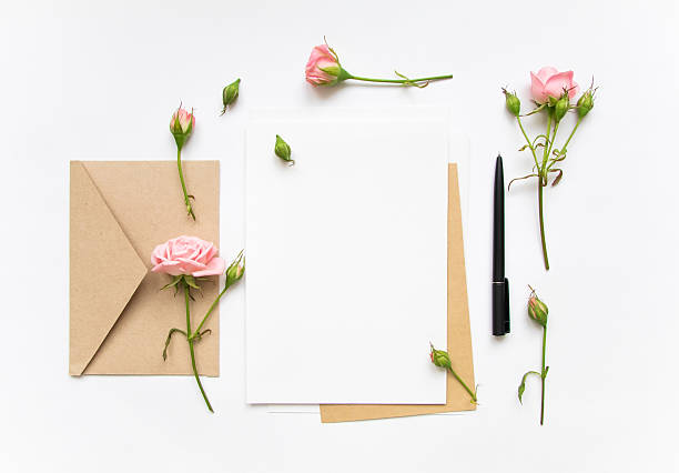 Letter and envelope decorated with pink roses. Holiday flat lay stock photo