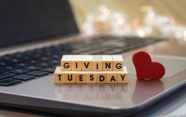 dar martes concepto de bloques de letras en el teclado del ordenador portátil - giving tuesday fotografías e imágenes de stock