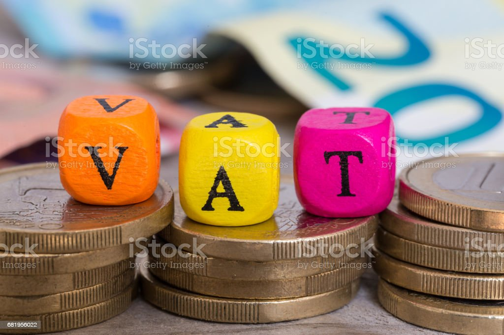 VAT letter cubes on coins concept stock photo
