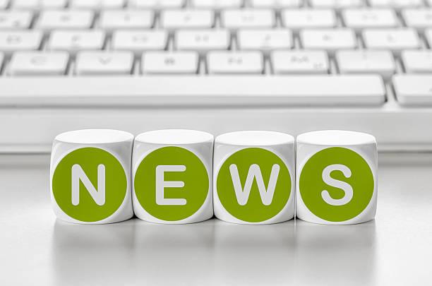Carta de dados en frente de un teclado de noticias - foto de stock