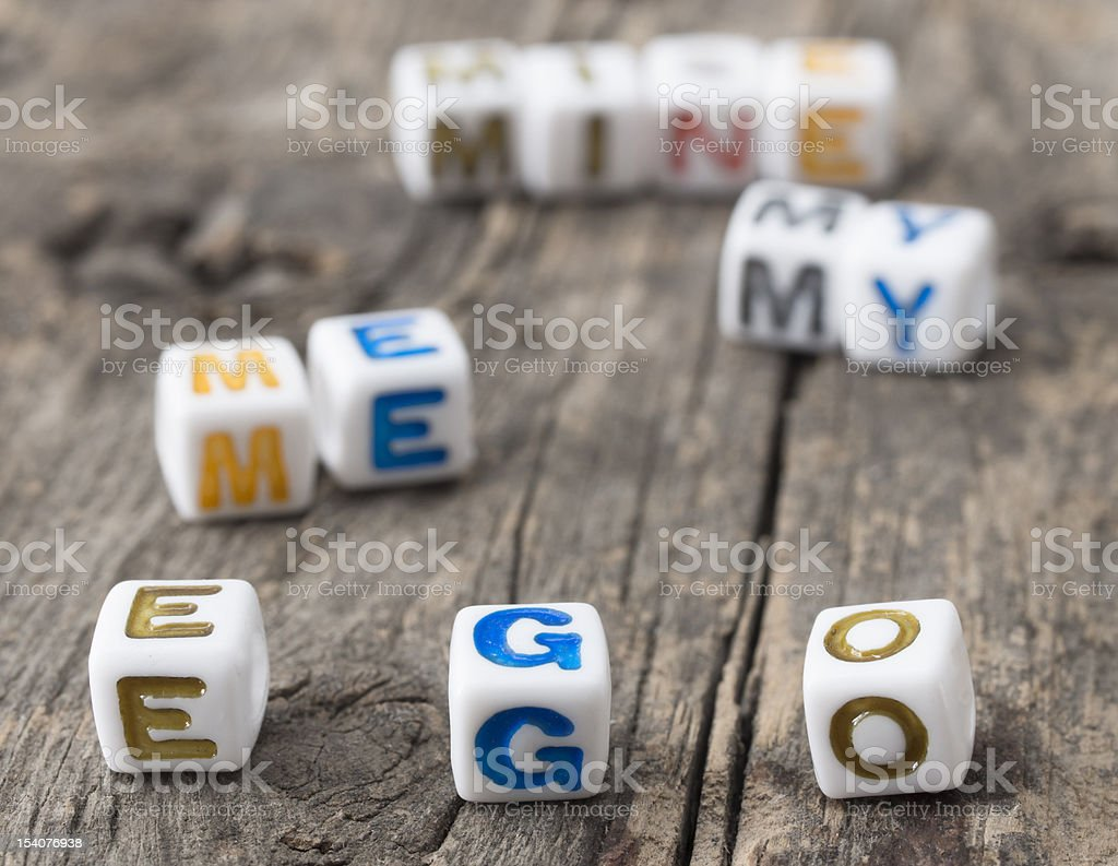 Letter dice spelling ego on a rustic wooden table stock photo