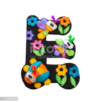 istock Letter E made in black foamy decorated with toy butterflies made in foamy and blue, yellow and orange flowers 1152509489