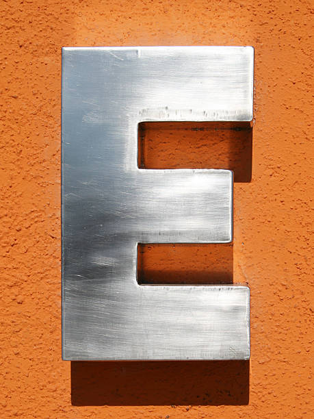 Letter E 3D metallic E letter over orange background letter e stock pictures, royalty-free photos & images