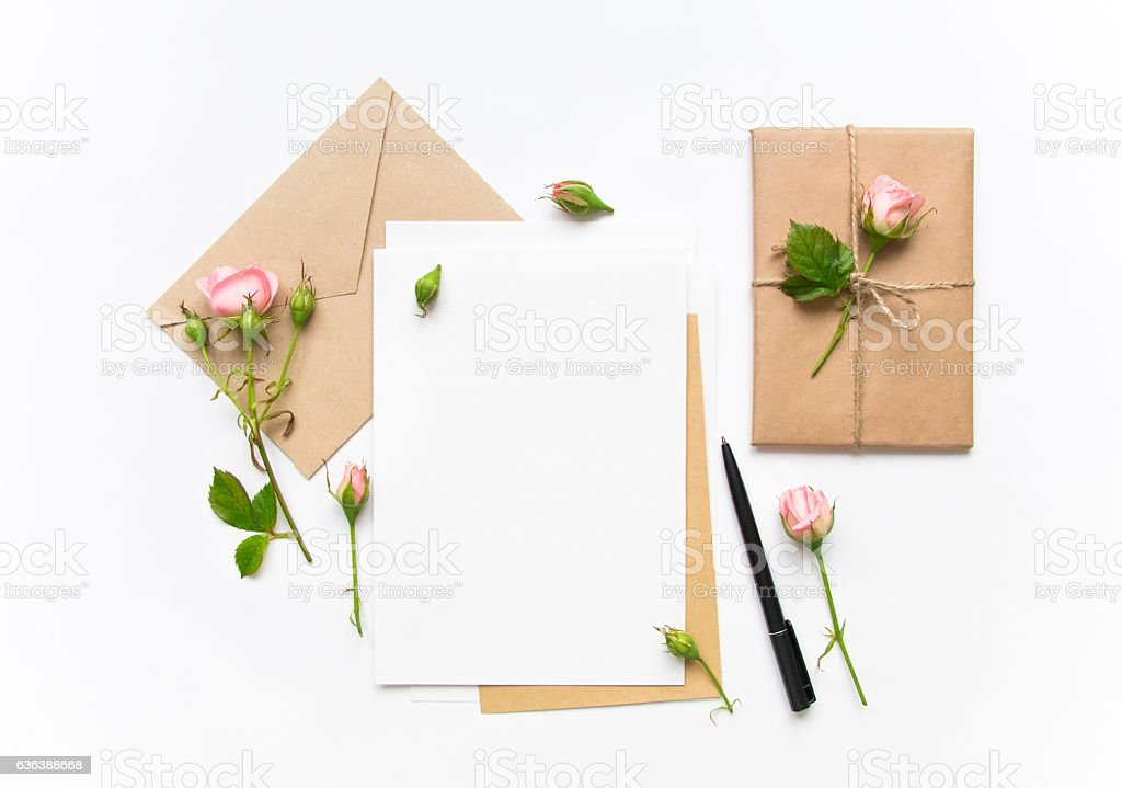 Letter, envelope and gift with roses. Holiday concept, top view stock photo