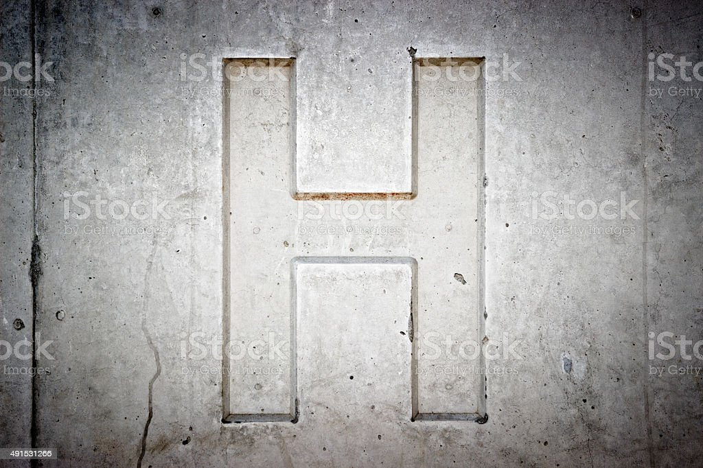 Letter H on concrete wall stock photo