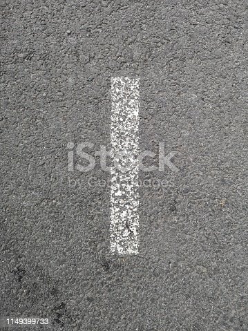 The letter I has been stenciled on a gray asphalt background with space all around for other graphic elements