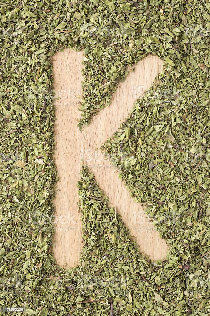 Letter K written with oregano royalty-free stock photo