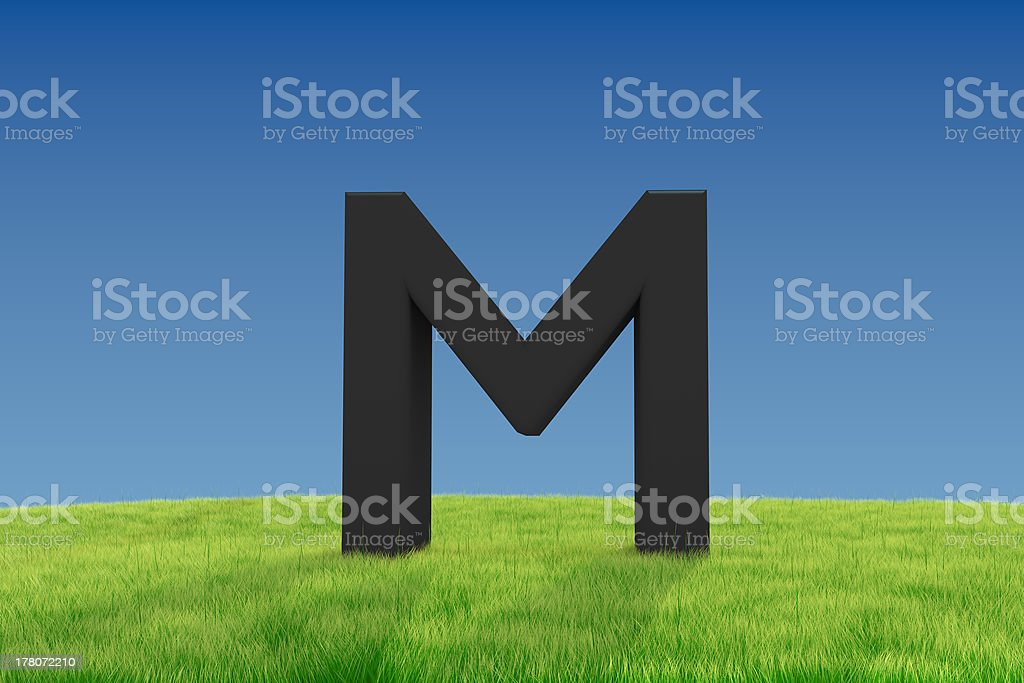 Letter M on green grass royalty-free stock photo