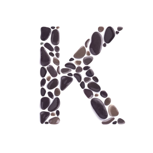 K Letter made of black beach stones isolated on white background K Letter made of dark beach stones isolated on white background k logo stock pictures, royalty-free photos & images