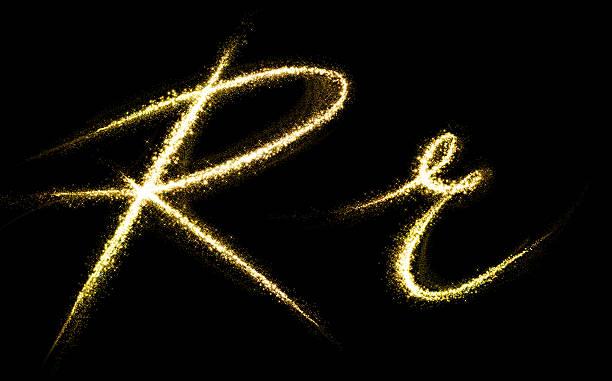 R letter of gold glittering stars dust flourish tail stock photo