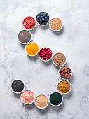 Above view of various superfoods in smal bowl in form S letter on gray background. Superfood as chia,spirulina,cocoa bean,goji,hemp,blueberry,quinoa,bee pollen,black sesame,turmeric. Top view,flat-lay